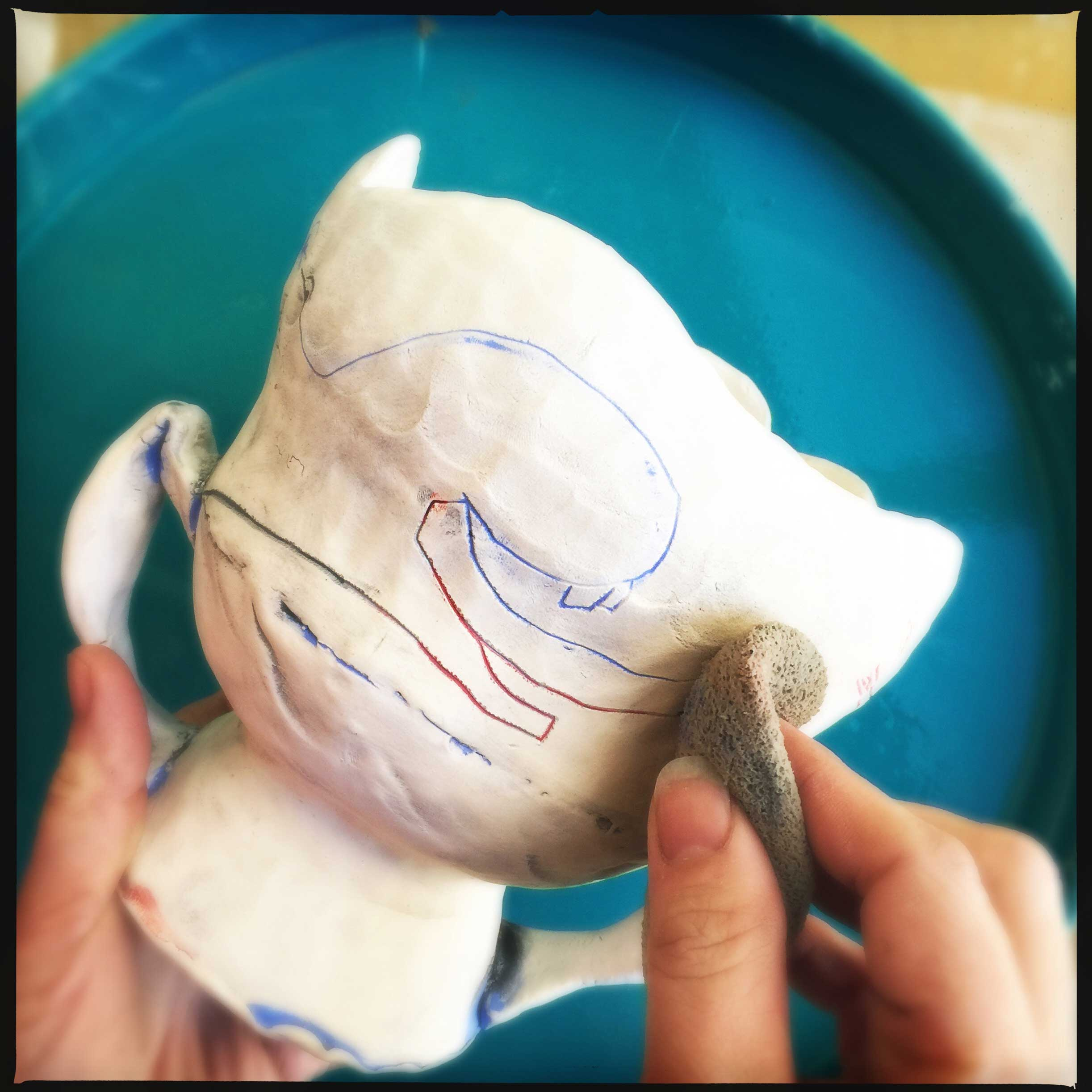 Cambric applies her underglaze to a bisque piece and wipes off the excess. Photo by artist, 2015.