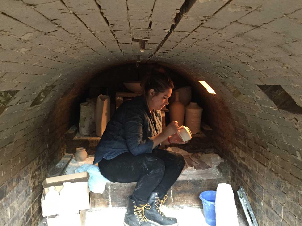 Jacklyn Scott helps load Muller's kiln.