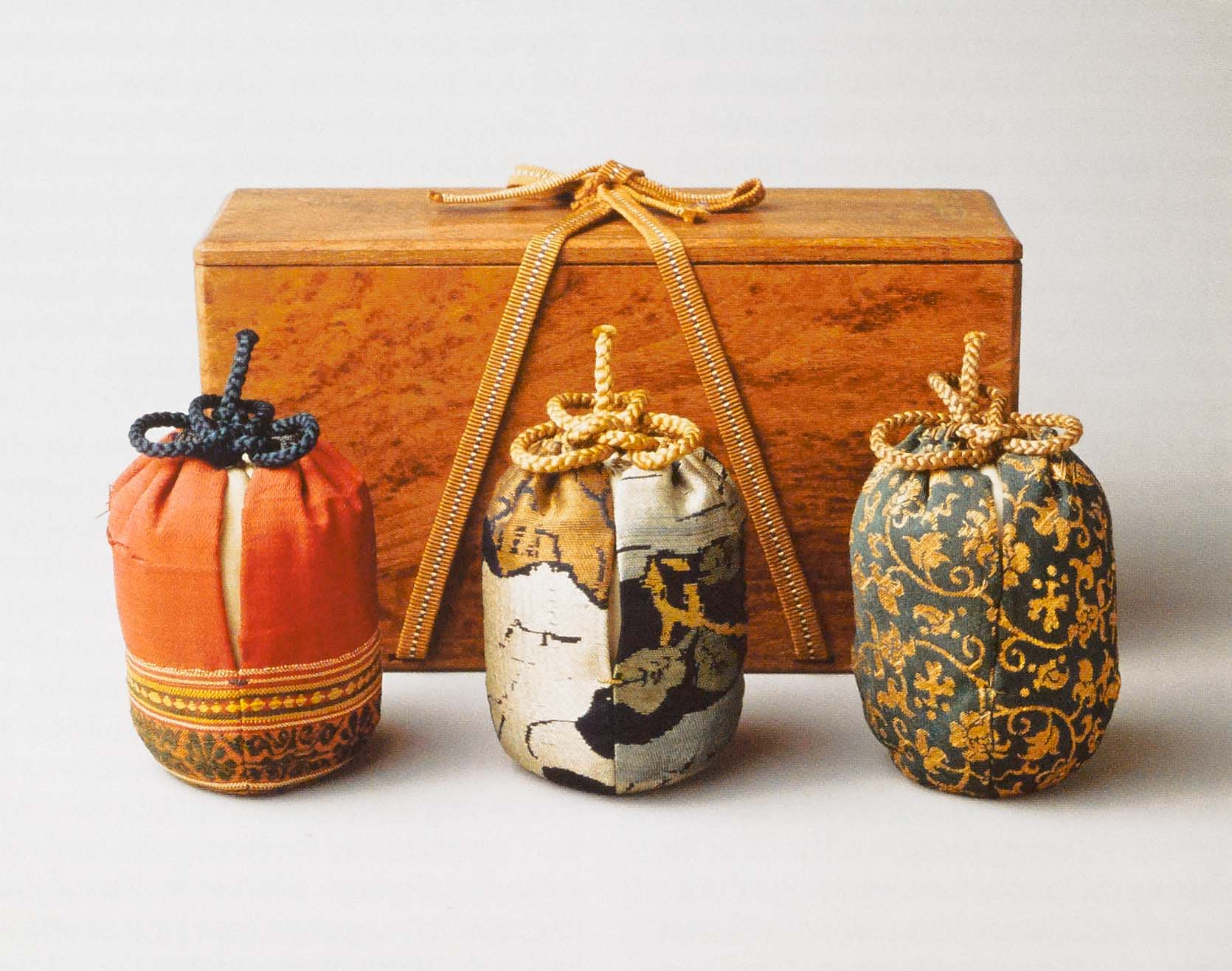 The three silk display bags with their box. Left: the informal bag of Satsuma Canton (Indian silk); center: the formal bag of Kiyomizu fragment (Chinese silk); right: the intermediate bag of gold brocade (Chinese silk).