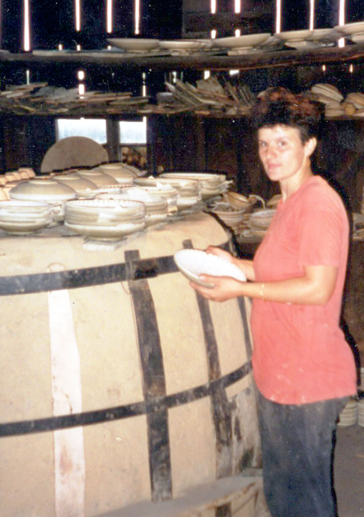 Alina Iorga, 1997, in her kiln building; pots are drying on top of the kiln.