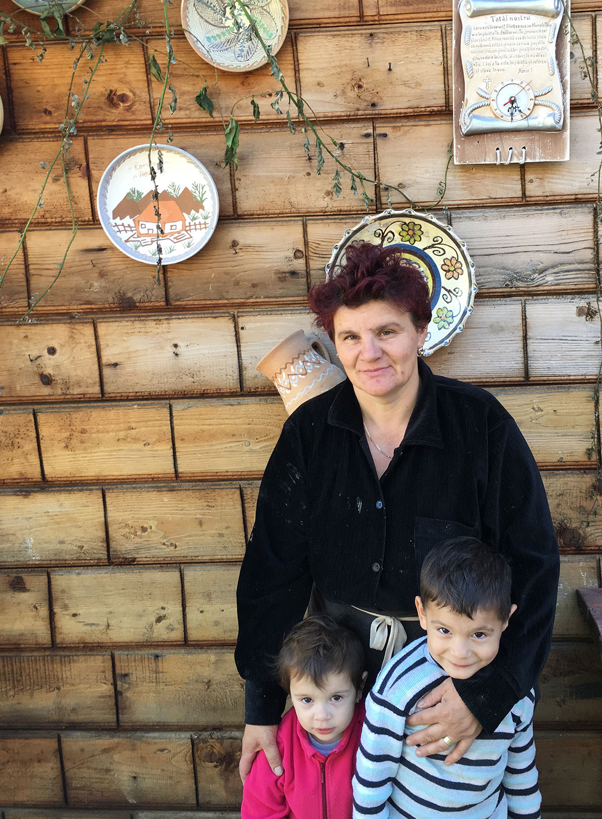 Alina Iorga, 2017, outside of her home with her grandchildren.