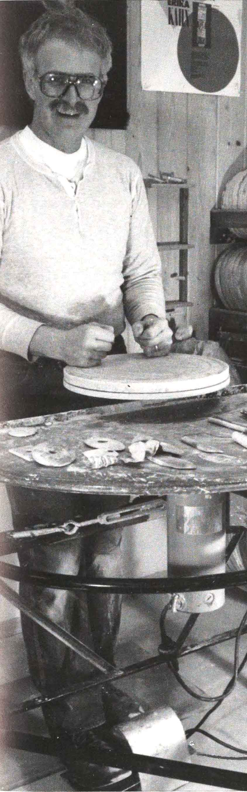 John Glick at his potter's wheel, raised to enable throwing pots standing, rather than sitting, for back health.