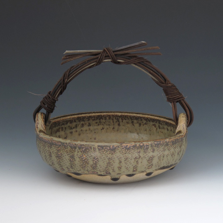 Basket with cane handle and ash glaze by Stewart.