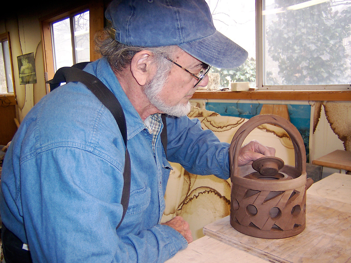 Norm Schulman working on a double wall teapot in studio, 2003