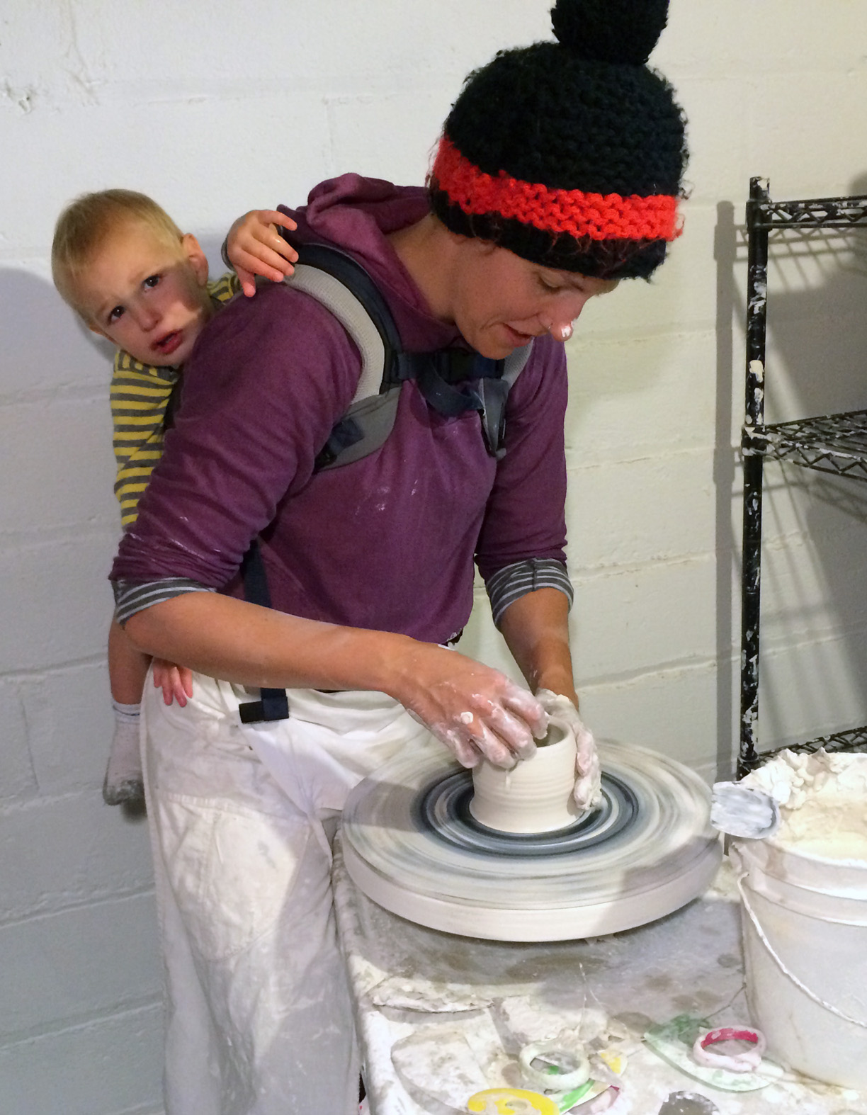 Kate Fisher with her son in her studio, at the potter's wheel.