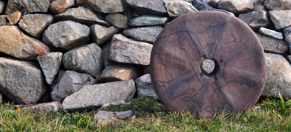 Ashwini Bhat's Millstone I, 2015, in front of the stonewall rebuilt by Dr. Robert French by the Slocum river, Westport, Massachusetts. Stoneware, 26 in. diameter. Photo by author.