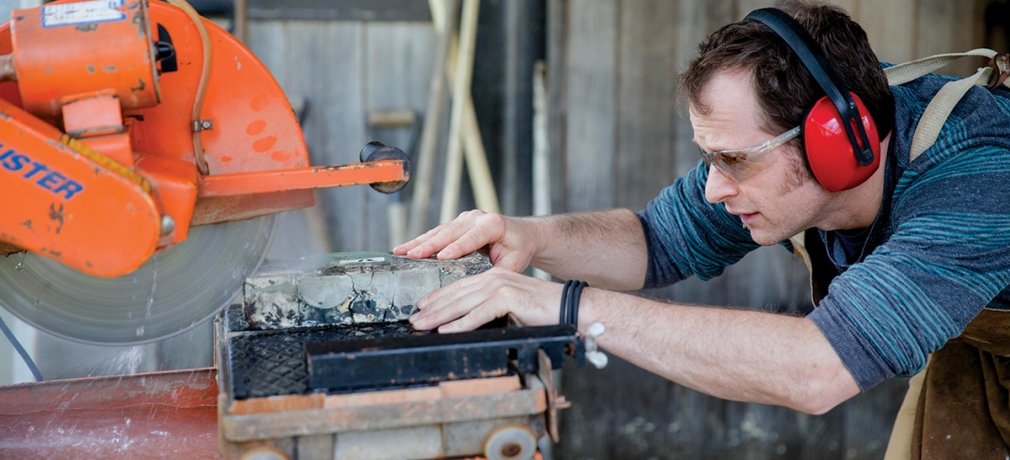 Mess slices a fired sculpture from his Reclaim series on a diamond wet saw outside his home studio. Photograph by Erin Little, May 2015.