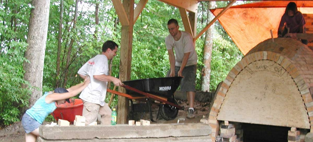 Simon Levin is assisted up the side berm during the construction of the anagama kiln at Corning Community College, Corning, New York, in 2003. Photograph by Dr. Robert Tichane.