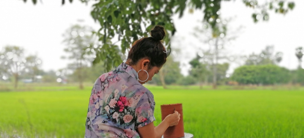 Sa Wanphet sits beside a rice paddy and experiments with surface texture on clay vase Sukhothai, Thailand, 2017. All photographs courtesy of Sa Wanphet.