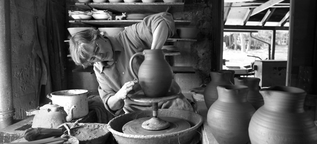 Jane Herold bowing handles on jugs in her studio, Palisades, New York. Photo by Susan Stava.