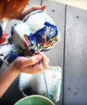 Cambric applies her luster overglaze to her footed bowls. Photo by artist, 2015.